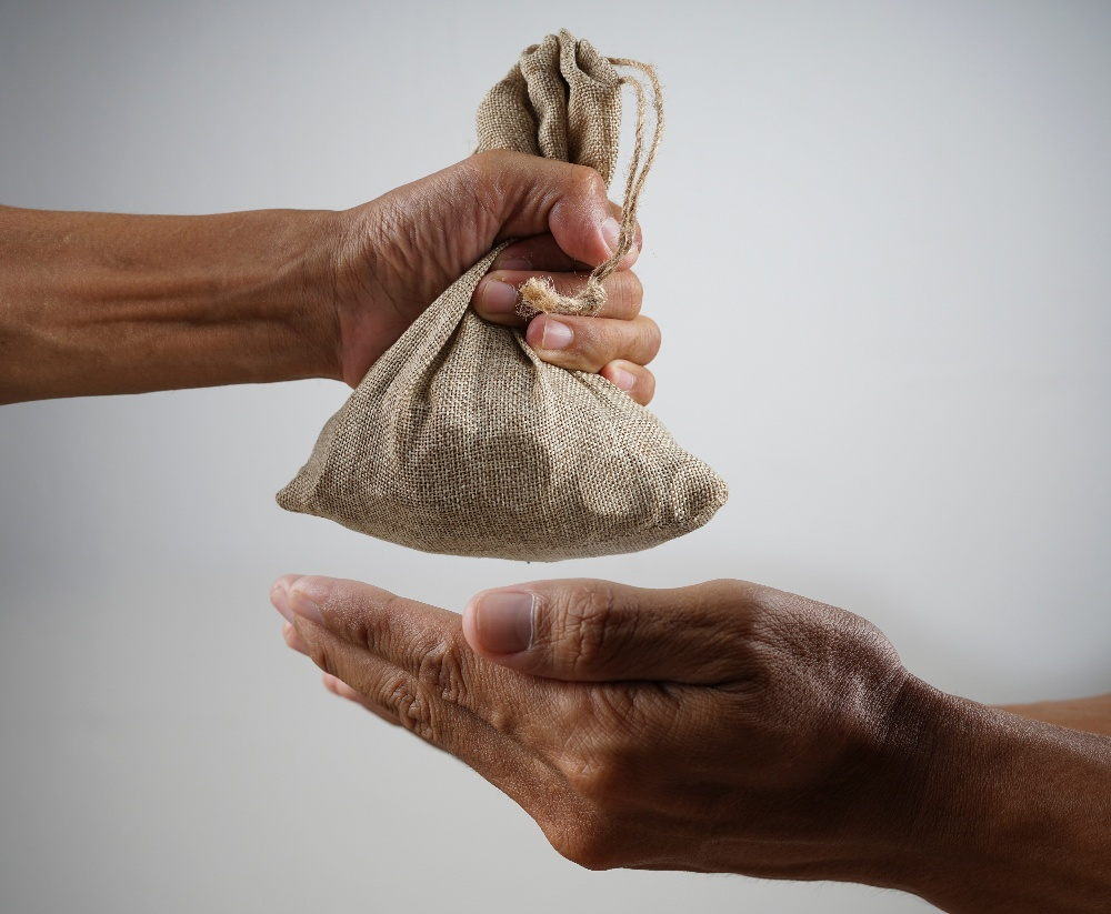 A donor giving a bag of money