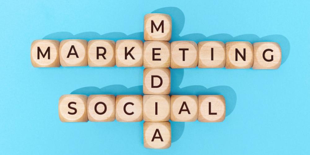 """""""Social Media Marketing"""" spelled on wooden letter blocks on blue background."""