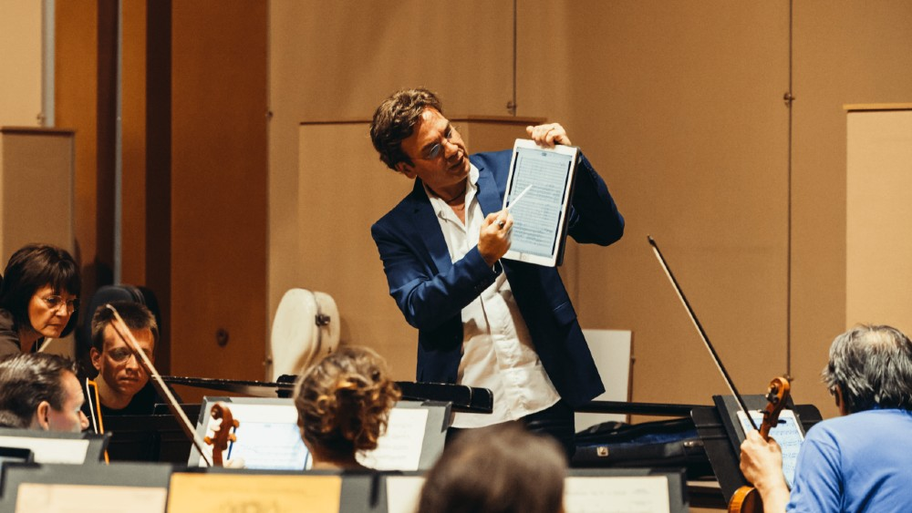 conductor showing digital score to musicians