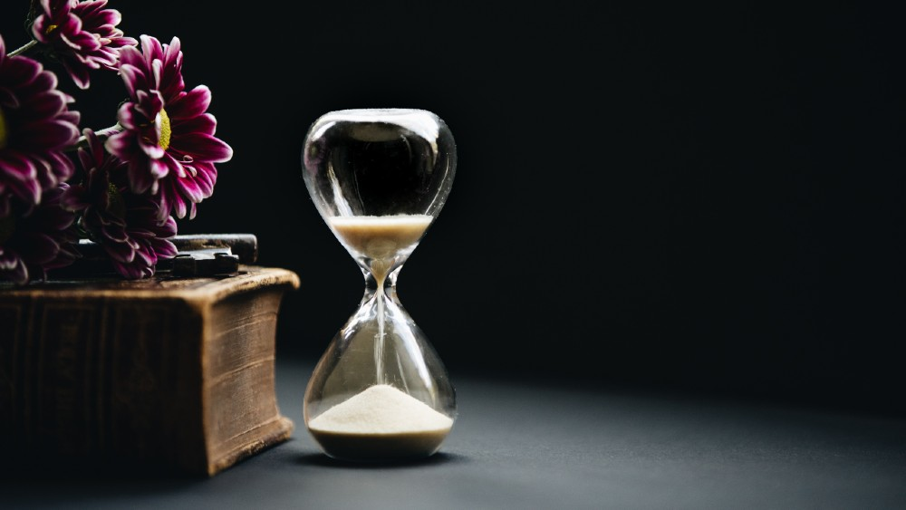 hourglass with sand next to purple floral arrangement