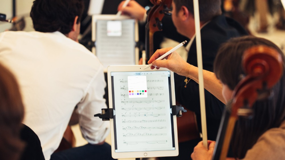 orchestra player making markings in digital score