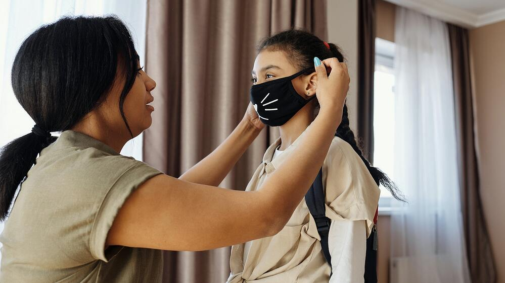 Parent putting mask on child